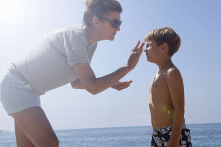 Mother applying sun protection on son