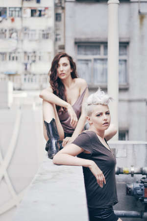 Portrait of  two young women on apartment rooftop LANG_EVOIMAGES