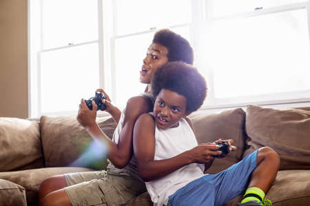 Two brothers back to back whilst playing game controllers in living room LANG_EVOIMAGES