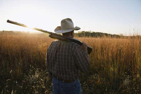 environmental issues: Senior male farmer with shotgun on shoulder in remote field at dusk, Plattsburg, Missouri, USA LANG_EVOIMAGES