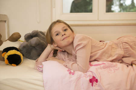 Portrait of mischievous girl lying on bed LANG_EVOIMAGES