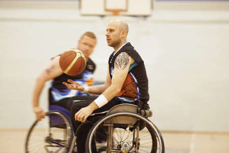 Wheelchair basketball player bouncing ball