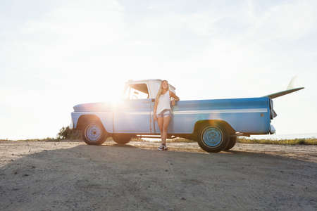 leaning on the truck: Portrait of young female surfer leaning against pickup truck at beach, Encinitas, California, USA