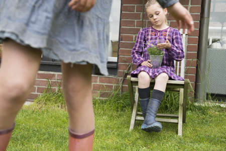 Girl on garden seat gazing at flower pot plant LANG_EVOIMAGES