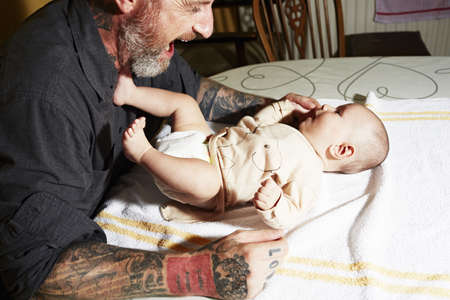 Father entertaining baby son lying on living room table
