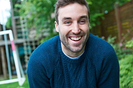 Man laughing in garden LANG_EVOIMAGES