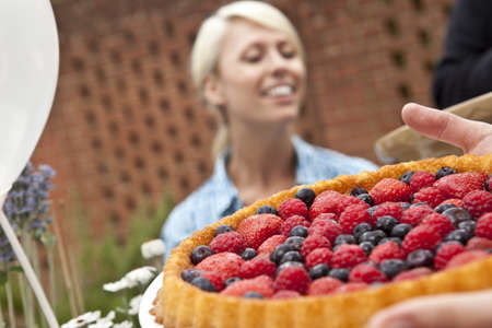 Two female friends with fruit flan at garden party