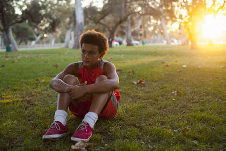 dream land: Sad looking boy sitting in park LANG_EVOIMAGES