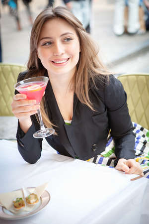 Young woman sitting at table at outdoor restaurant holding cocktail