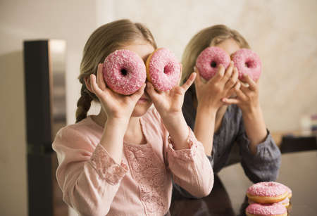 Portrait of two sisters with doughnut holes over their eyes LANG_EVOIMAGES