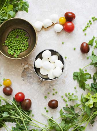 Still life of bowls of mozzarella cheese and peas with tomatoes and parsley
