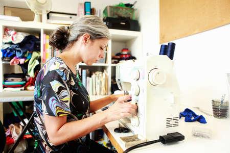 sewing machines: Designer working at sewing machine in studio LANG_EVOIMAGES