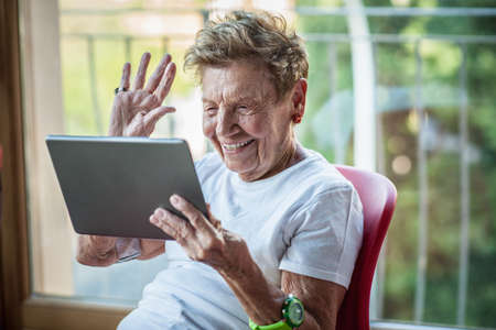 A very senior woman using digital tablet on apartment balcony