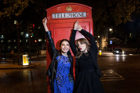 Two young female friends dancing in front of red phone box at night, London, UK