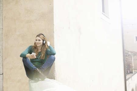 Young woman sitting cross legged listening to music through headphones