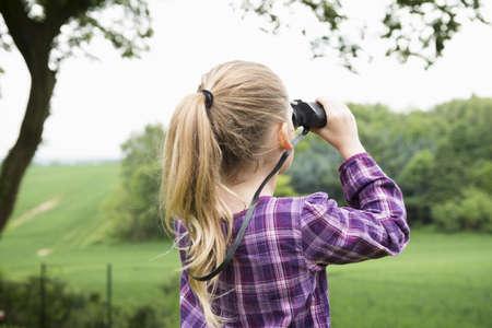Girl using binoculars LANG_EVOIMAGES