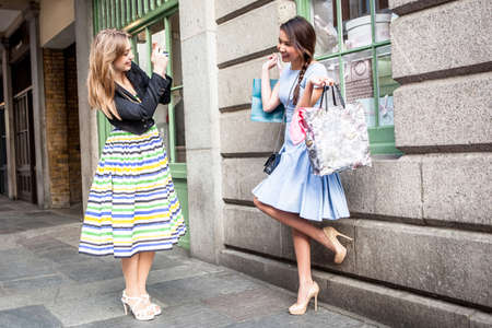 Young woman taking photograph of friend carrying shopping bags