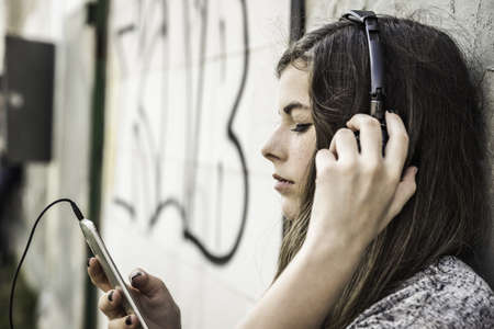 casual clothing 12 year old: Girl listening to music on smartphone LANG_EVOIMAGES
