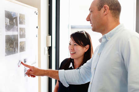Male and female architects looking at blueprints on office wall