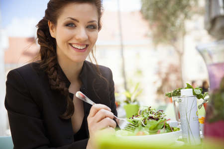 Young adult woman eating salad, outside