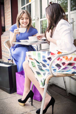 Two young women sitting outside cafe, drinking coffee
