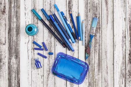 Still life of blue paint brush, crayons and colored pencils