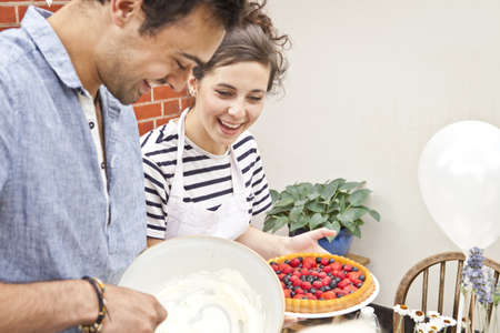 Young couple preparing fruit flan and meringue at garden party LANG_EVOIMAGES