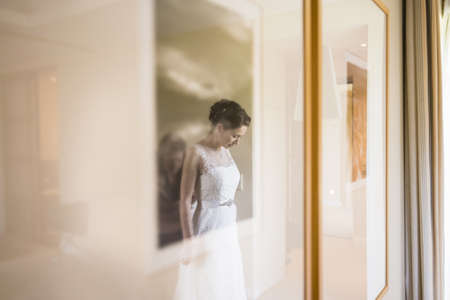 Reflection of female friend zipping up brides wedding dress in hotel