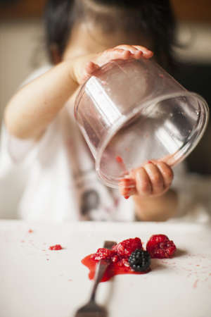 casual clothing 12 year old: One year old baby girl holding fruit container upside down in highchair LANG_EVOIMAGES