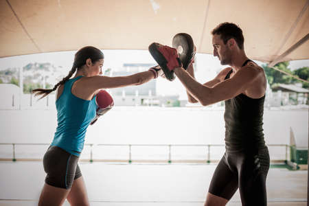 Young woman boxing with personal trainer