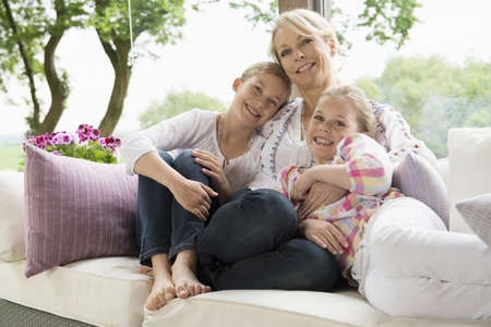 Mother and daughters sitting on sofa