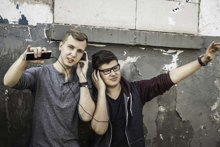 Teenage boys listening to music by abandoned building