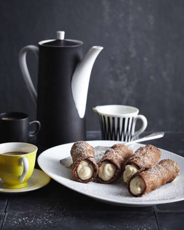 Plate of ricotta cannoli with pot of coffee LANG_EVOIMAGES