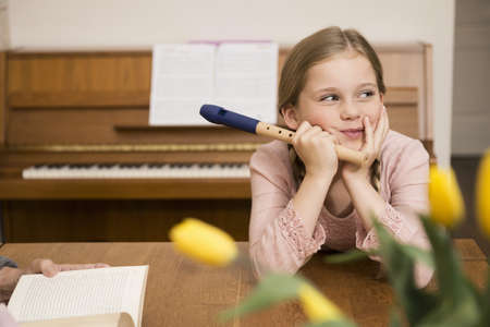 Bored distracted girl with recorder instrument in dining room