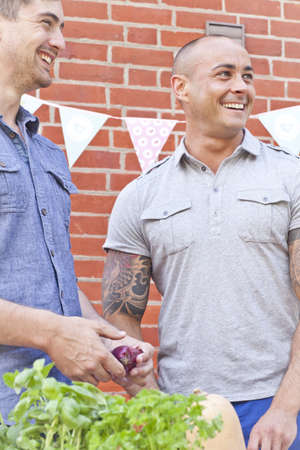 Two male friends laughing and preparing food for garden barbecue