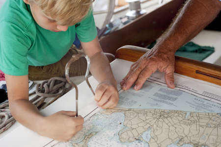 Boy and grandfather using dividers on navigation maps in sailboat cabin