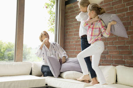 Mother with daughters having pillow fight