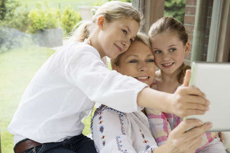 Mother and daughters using digital tablet LANG_EVOIMAGES