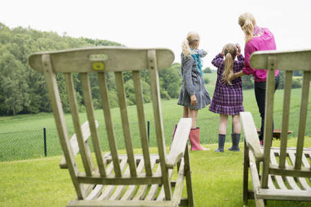 Mother and daughters using binoculars, chairs in foreground