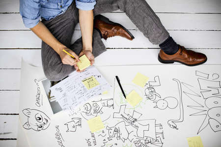 top animated: Graphic designer producing creative ideas on floor LANG_EVOIMAGES