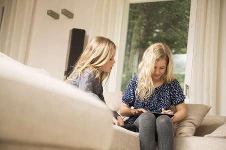Two sisters using digital tablet