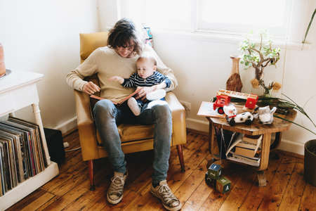 Father sitting on sofa with son