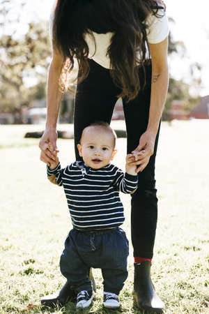 Woman supporting son in first steps LANG_EVOIMAGES