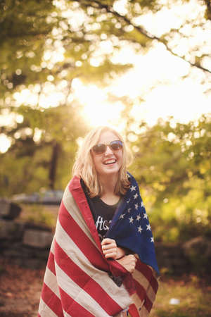 Young woman wrapped in US flag, portrait