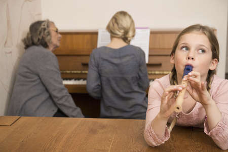 Girl playing recorder while sister on piano watched by grandmother LANG_EVOIMAGES