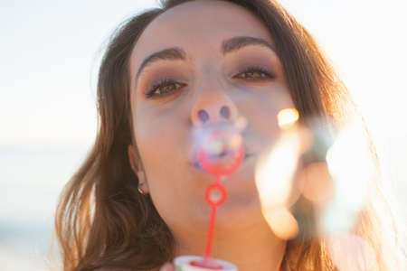 Close up of young woman blowing bubbles on beach, Castiadas, Sardinia, Italy