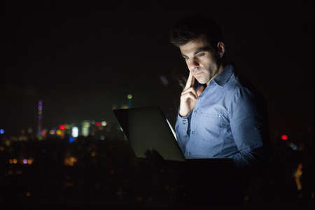 Young businessman looking at laptop in front of skyscraper office window at night, Shanghai, China
