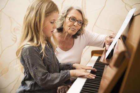 Grandmother teaching granddaughter piano LANG_EVOIMAGES
