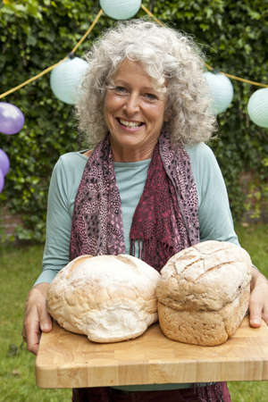 Portrait of mature woman with loaves of bread at garden party
