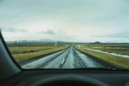 Straight rural road through car windscreen, Vesturland, Iceland